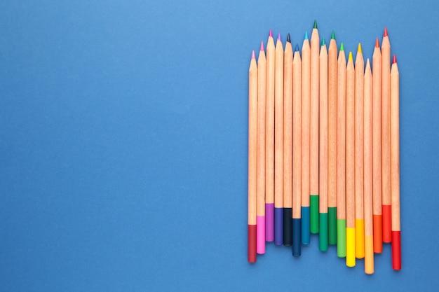 Kolorowe kredki na niebieskiej ścianie z miejsca na kopię. widok z góry.