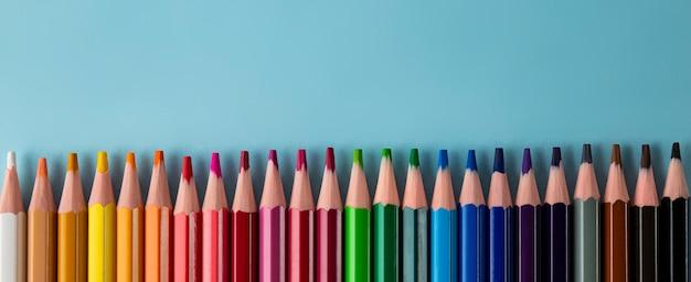 Kolorowe kredki na niebieskim banerze internetowym z miejscem na tekst copy