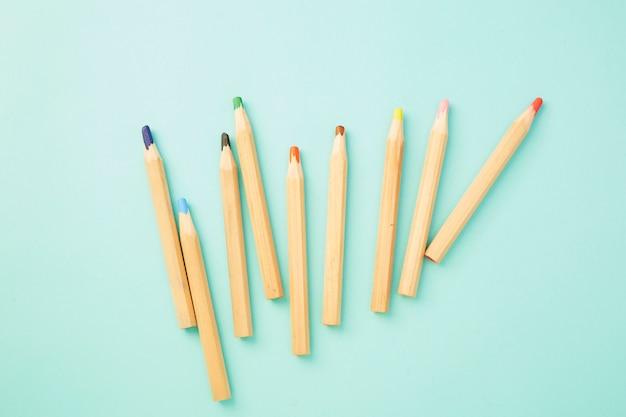 Kolorowe kredki na pastelowym bladoniebieskim