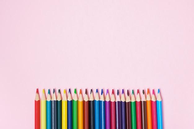 Kolorowe kredki na różowym tle widok z góry miejsca kopiowania