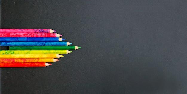 Kolorowe kredki na tablicy szkolnej