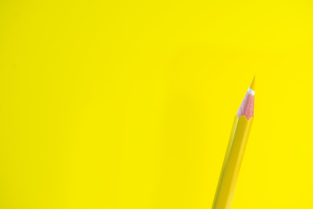Kolorowe kredki na żółtym tle z miejsca na tekst.
