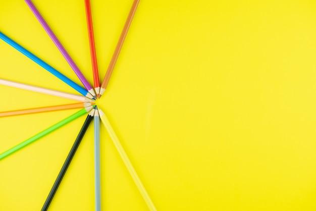 Kolorowe kredki na żółtym tle.