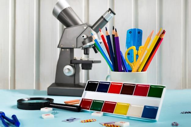 Kolorowe kredki, nożyczki, linijka, mikroskop, farby na niebieskim tle. zestaw przyborów szkolnych, przybory szkolne