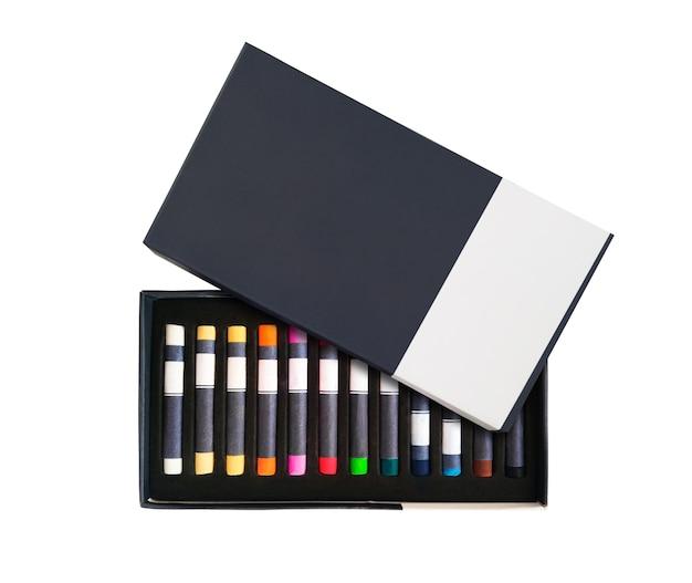 Kolorowe kredki pastelowe lub ołówki w pudełku z miejscem na kopię i na białym tle