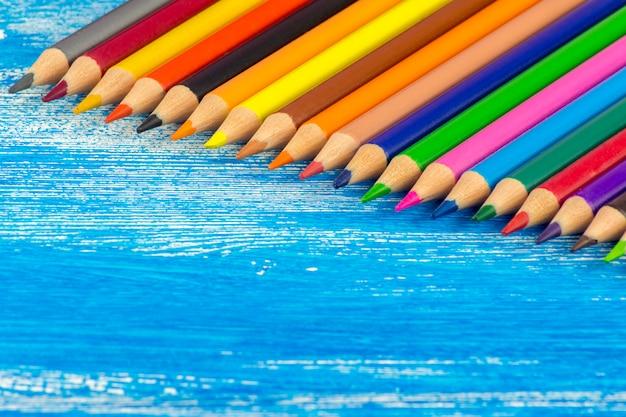 Kolorowe kredki są na niebieskim pokładzie.