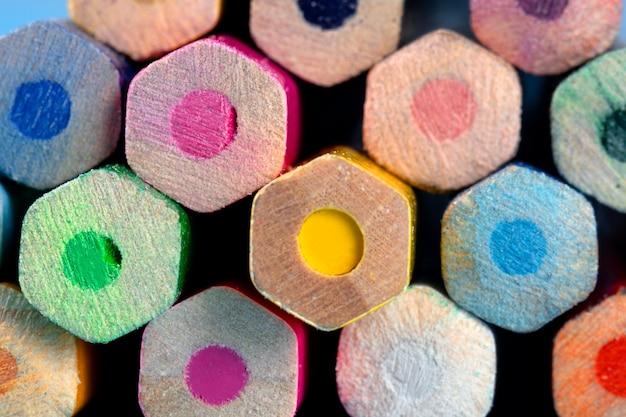 Kolorowe kredki są ułożone jedna na drugiej, wygląd z końca. zbliżenie. tło kolorowych ołówków