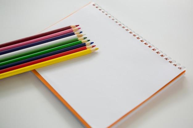 Kolorowe kredki trzymane na spiralnej książce