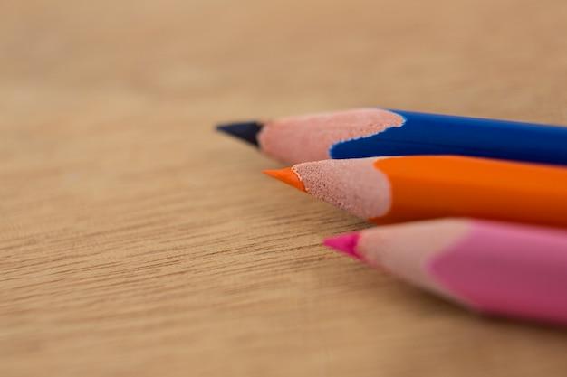 Kolorowe kredki ułożone ukośnie na drewnianym stole