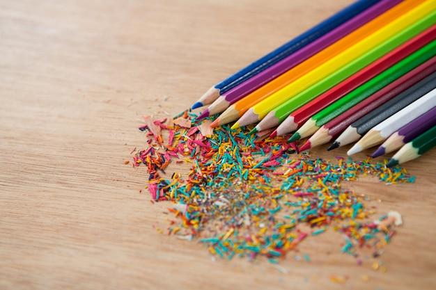 Kolorowe kredki ułożone ukośnie z wiórkami ołówkowymi