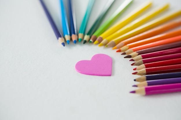 Kolorowe kredki ułożone w półkole z sercem