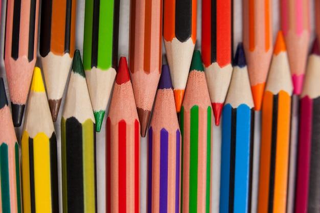 Kolorowe kredki ułożone we wzór interlock na białym tle