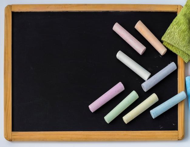 Kolorowe kredki umieszczone są na czarnej desce kreślarskiej dla dzieci z kopią przestrzeni.