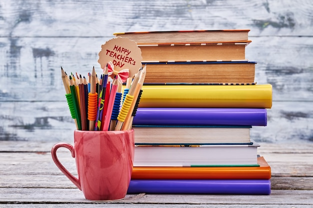 Kolorowe kredki w czerwonej filiżance. stos kolorowych książek. gratulacje dla najlepszego nauczyciela.