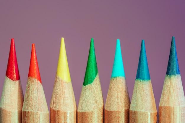 Kolorowe kredki w kolorach tęczy z bliska w modnym świetle neonowym.