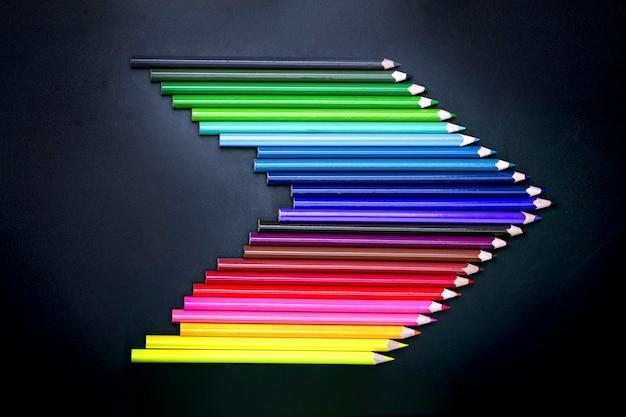 Kolorowe kredki w kształcie strzałki na białym tle