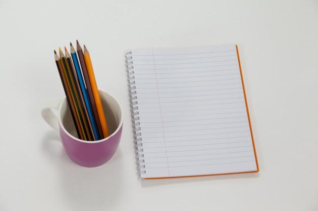 Kolorowe kredki w kubku oraz notes