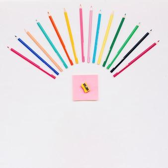 Kolorowe kredki w pobliżu karteczek i temperówka