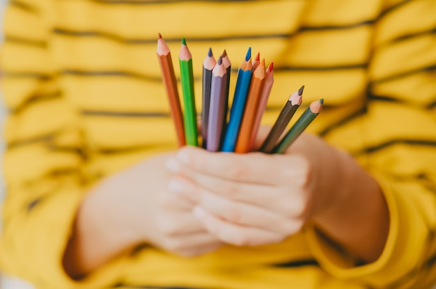 Kolorowe kredki w rękach małego chłopca. jasne zdjęcie z ołówkami do rysowania. fotografia o tematyce szkolnej