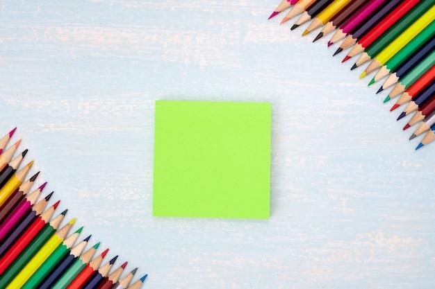 Kolorowe kredki w rogu z notatką w niebieskiej ramce
