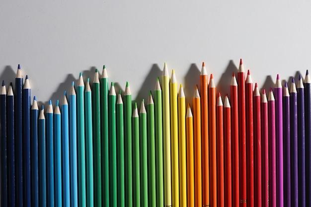 Kolorowe kredki w różnych odcieniach leżą w rzędzie na białym tle