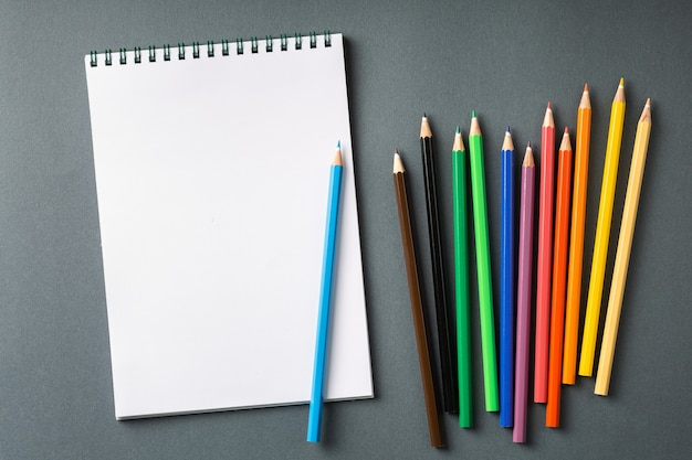 Kolorowe kredki w rzędzie na białym tle na widoku z góry szarej ścianie. notatnik na spirali z kolorowym ołówkiem na pustym stole. koncepcja płaskiego świeckich