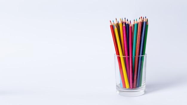 Kolorowe kredki w szklance na białym stole.
