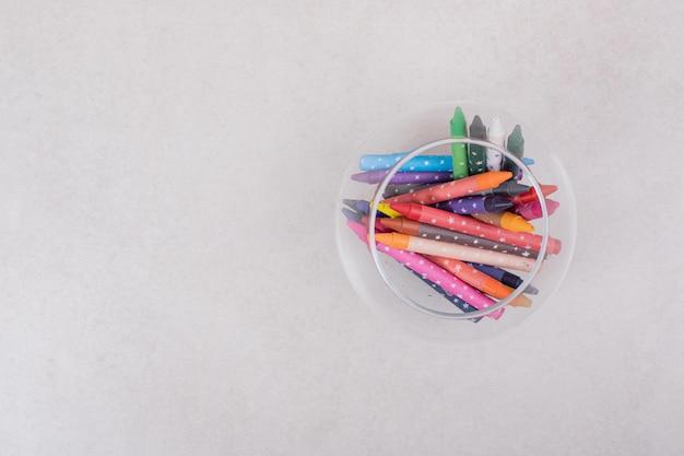 Kolorowe kredki w szkle na białej przestrzeni