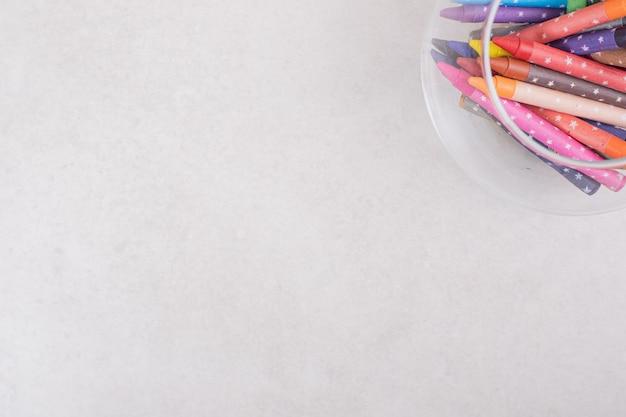 Kolorowe kredki w szkle na białym tle