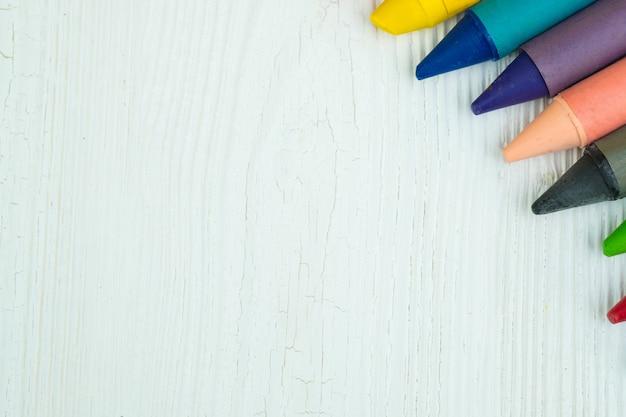 Kolorowe kredki woskowe ołówki na biały stół z drewna z miejsca na kopię.