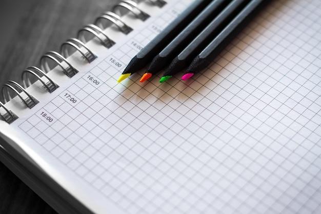 Kolorowe kredki z notatnikiem na biurku