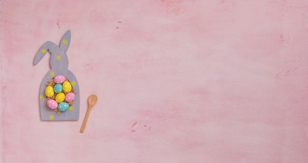 Kolorowe kropki pisanki w ramce w kształcie królika na różowym tle betonu
