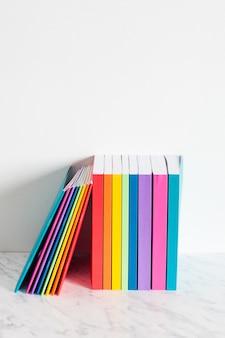 Kolorowe książki nakreślone są kolorami tęczy. ułożone w stos książek na półce w pobliżu białej ściany