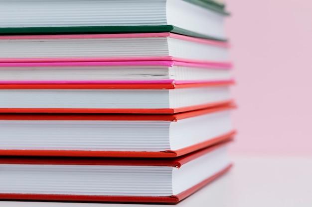 Kolorowe książki z różowym tłem z bliska