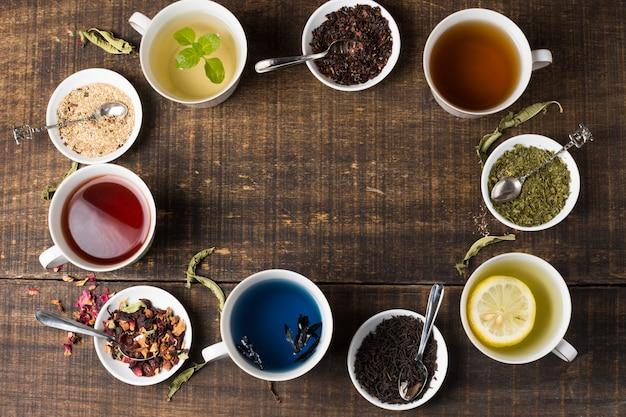 Kolorowe kubki z herbatą aromatu ułożone w okrągłej pozycji na drewnianym biurku