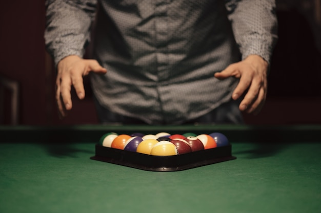 Kolorowe kulki amerykańskiego bilarda w trójkącie na stole bilardowym i gracz w bilard z bliska