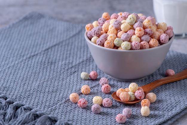 Kolorowe kulki kukurydziane zbóż mix, słodycze miska o smaku owocowym na szarym tle cementu, bliska, świeże, smaczne i zdrowe śniadanie, skopiuj koncepcja projektowania przestrzeni.