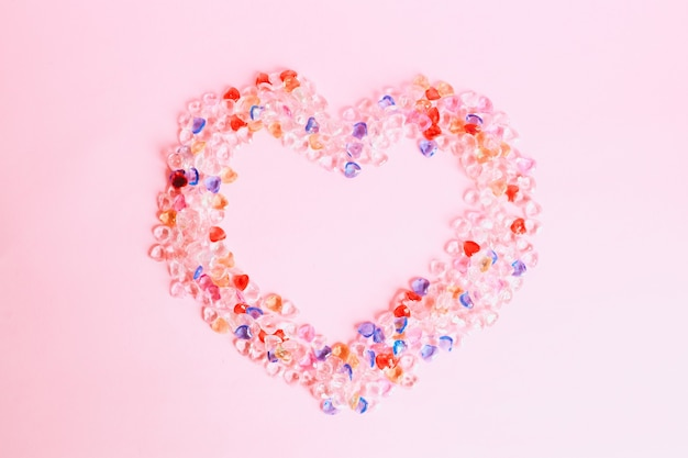 Kolorowe kulki w kształcie serca na białym tle na różowym tle