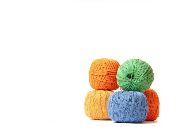 Kolorowe kulki z szydełkowej nici na białym tle