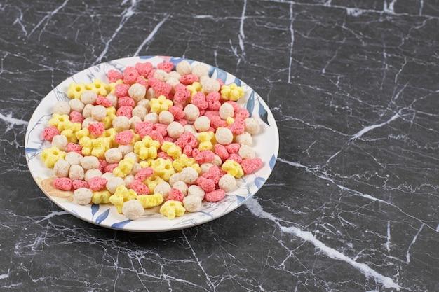 Kolorowe kulki zbożowe na białym talerzu.