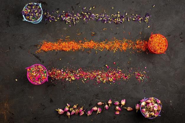 Kolorowe kwiatowe kawałki wielokolorowe w doniczkach i rozłóż widok z góry na ciemnym biurku