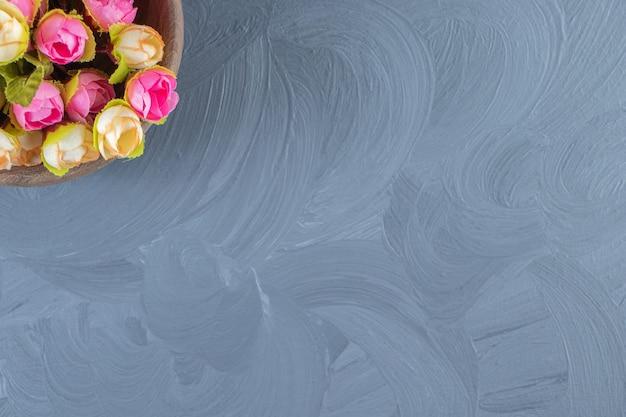 Kolorowe kwiaty w misce, na białym tle.