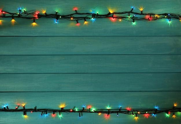 Kolorowe lampki choinkowe na tle drewnianych desek