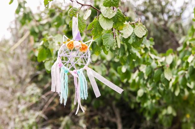 Kolorowe łapacz snów na zewnątrz na tle przyrody lato. ręcznie wykonany wystrój z piór, wstążek, nici i koralików.