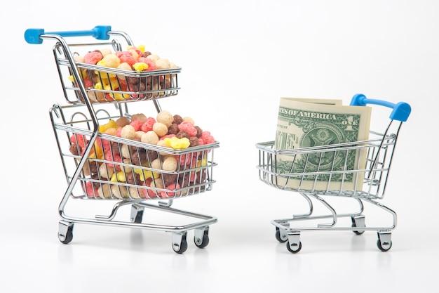 Kolorowe lekkie przekąski w koszu targowym i banknoty dolarowe na białym tle