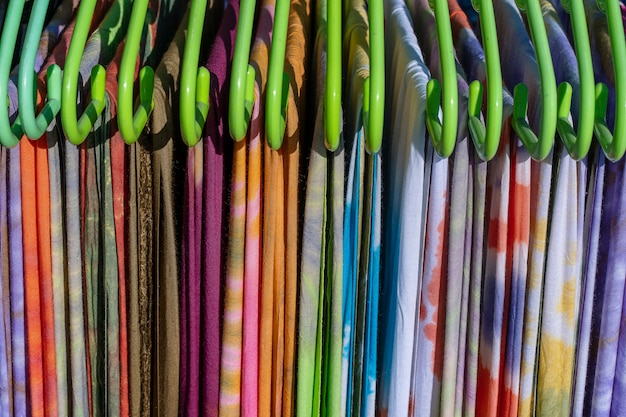 Kolorowe letnie ubrania na wieszakach na sprzedaż na lokalnym targu ulicznym w tajlandii, zbliżenie