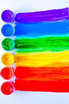 Kolorowe linie narysowane poziomo z puszek z farbą w formie tęczy na białym tle...