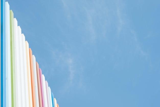 Kolorowe listwy stalowe zdobią projekt wydatną ścianę i błękitne niebo w słoneczny dzień.