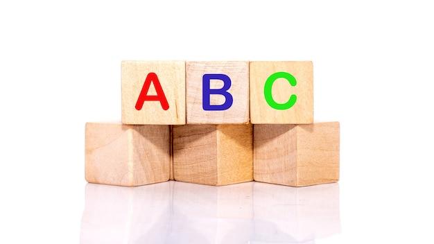 Kolorowe litery abc na drewnianych klockach, ułożone poziomo.