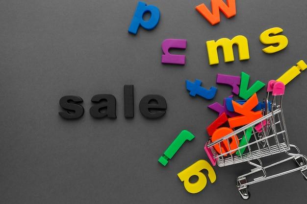 Kolorowe litery i widok z góry tacy na zakupy